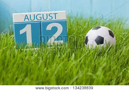 August 12th. Image of august 12 wooden color calendar on green grass lawn background with soccer ball. Summer day. Empty space for text.
