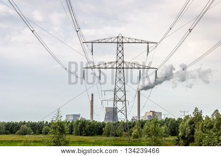 Power lines to the coal-fired power plant in the Netherlands. Smoke comes out of the chimney. Beside the plant is a concrete cooling tower.