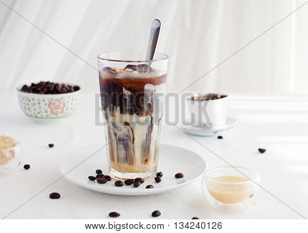 Ice coffee with condensed milk traditional Vietnamese Thai coffee with coffee beans on a white plate background