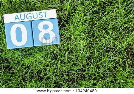 August 8th. Image of august 8 wooden color calendar on green grass lawn background. Summer day. Empty space for text.