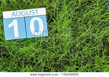 August 10th. Image of august 10 wooden color calendar on green grass lawn background. Summer day. Empty space for text.