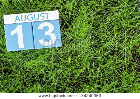 August 13th. Image of august 13 wooden color calendar on green grass lawn background. Summer day. Empty space for text.