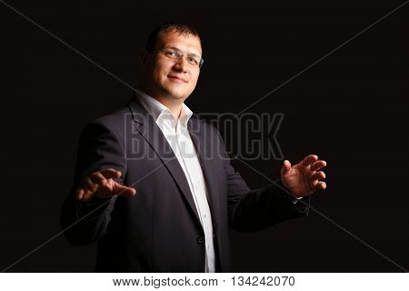 Young male businessman posing in studio on dark background.