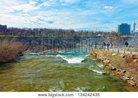 Niagara Falls, USA - April 29, 2015: Niagara Falls in US and View on Ontario in Canada near Niagara River. Niagara River is a border between the United States of America and Canada. Tourists nearby