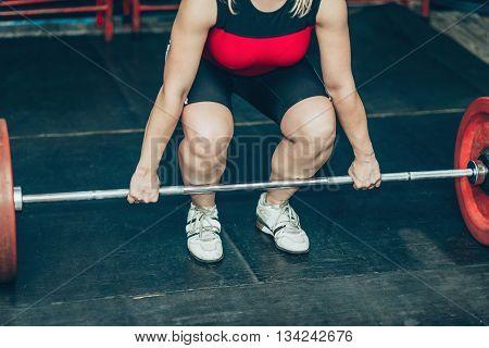 Female on weightlifting training, horizontal image, selective focus, indoors