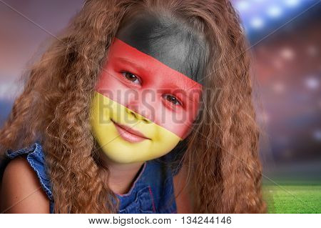 Soccer fan little smiling girl portrait with flag of Germany on face