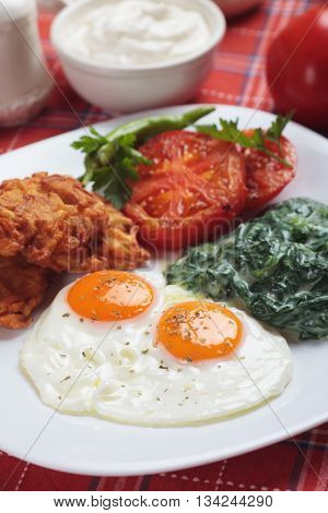 Fried eggs served for breakfast with spinach, tomato and potato pancakes