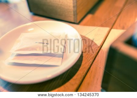 Two white sugar bags with small black text on white plate on wooden table in morning light selective focus on the letters with shallow depth of field color effect treatment in post for cinematic look