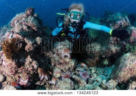 beautiful diver blonde girl diving in the deep blue sea while swimming underwater