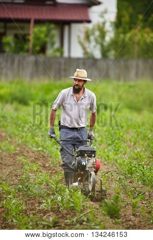 Young Farmer Weeding With A Tiller