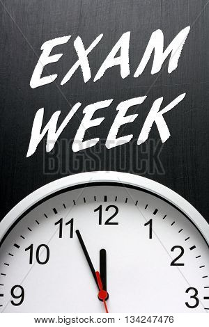The words Exam Week on a blackboard above a modern wall clock as a reminder