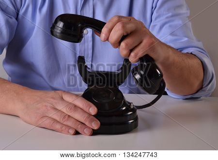 Man holding an old black telephone receiving a call, lifting handset telephone.