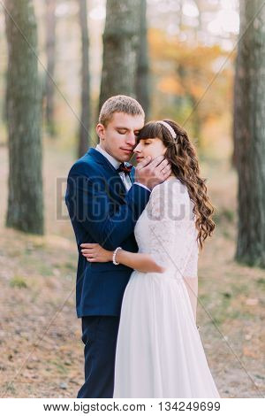 Happy romantic newly married couple embracing each other in the autumn pine forest.