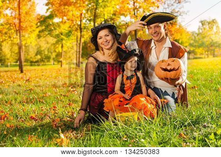 Family in Halloween costumes sit on the grass with pumpkin outside during beautiful sunny autumn day