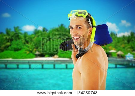 Young man with swimming mask or goggles with flippers on blurred resort background