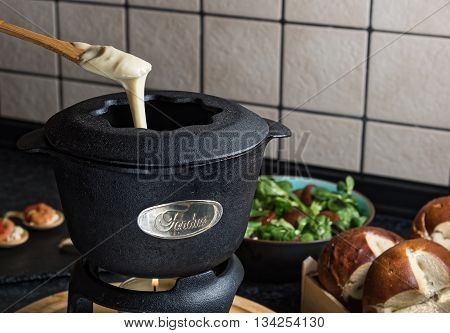 Cheese fondue preparation in kitchen with bread and salad