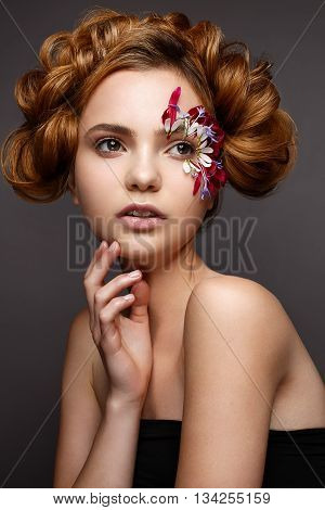 Beautiful girl with creative make-up with floral appliques. The model in the style of romantic with flower petals around her eyes. The photo was made in a studio. Beauty face
