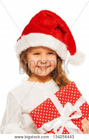 Close up portrait of smiling little girl with red present with white bow and wearing Christmas Santa hat