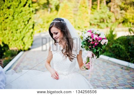 Cinderella bride with bouquet looking down at wedding day