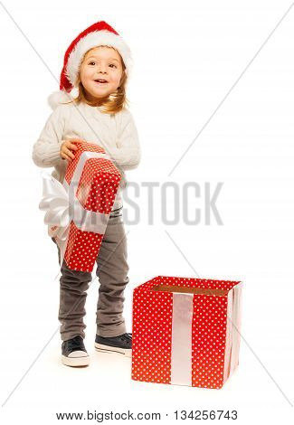 Amazed beautiful 3 years old blonde girl opening her gift and handling cover at her hand