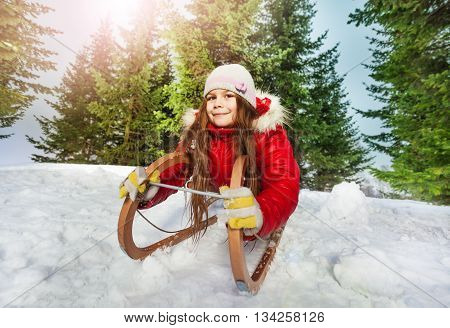 Happy girl with warm hat, hand gloves and scarf having fun on snow sledge, outdoors