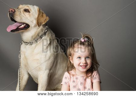 Happy little girl with smiling funny face playing labrador dog pet in studio on grey background