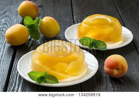 Fruit jelly with pieces of apricots and fresh apricots on an old wooden table. Selective focus