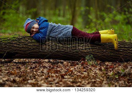 photo of little funny boy on big log