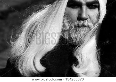 Druid old man with long silver hair beard with cat on shoulder in fur coat black and white on grey background