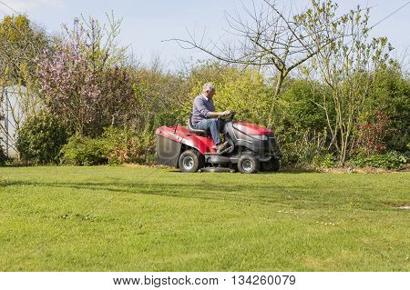 senior gardener mowing the lawn with tractor France