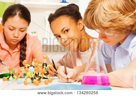 Three multi ethnic students writing chemical formula sitting at the desk in science class