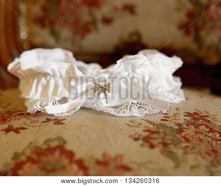 The garter of the bride laying on a pillow and prepared for wedding