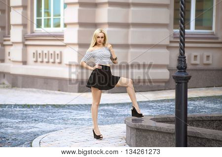 Beautiful blonde woman at the colorful summer city in the striped t-shirt posing on the street - photo with shallow dept of field
