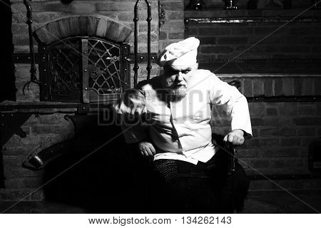 Senior male chief cook bearded man in uniform and hat sits at oven black and white on kitchen background