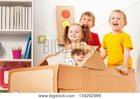 Group of four happy 5 years old kids playing drivers with handmade cardboard car at the kindergarten