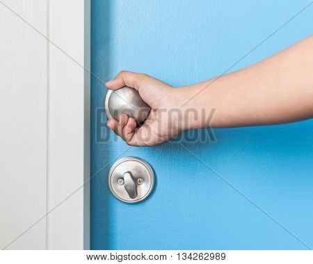 Hand Holding Metal Silver Doorknob On Wooden Door