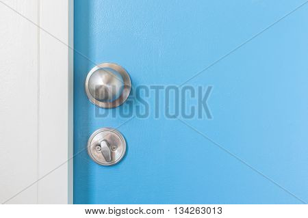 Closeup of metal silver doorknob on wooden door
