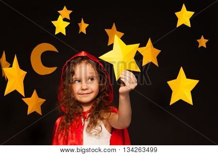 Little girl in red cape with hood holding big yellow paper star in her hand, standing against starry sky