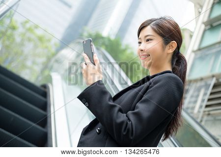 Business woman use of phone and standing on escalator