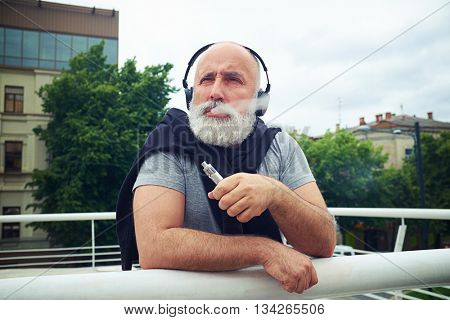 Stylish aged man in headphones is leaning on the handhold and smoking electronic cigarette on a cloudy day in city