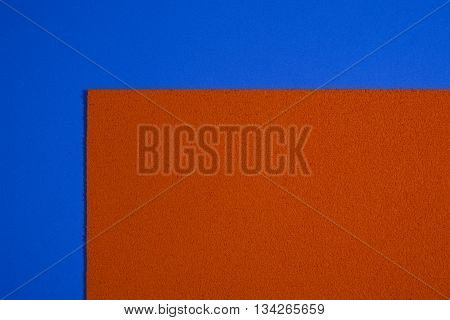 Eva foam ethylene vinyl acetate sponge plush orange surface on blue smooth background