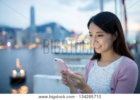 Asian woman sending sms text message on mobile phone