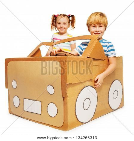 Cute five years old kids, boy and girl, playing the driver and the passenger with cardboard car, isolated on white