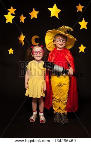 Full length photo of boy and girl in sky watchers costumes with a telescope, standing among handmade stars and moon