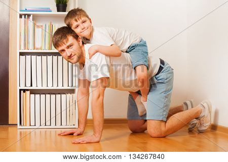 Smiling boy enjoys riding on father's back at home