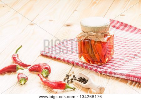preserved chili in glass jar on wooden table covered red squared napkin pepper wooden scoop copy space. free space for text