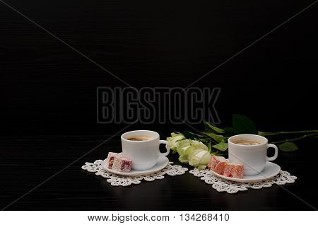 A couple cups of coffee with milk Turkish Delight a bouquet of white roses on a black background. Space for text