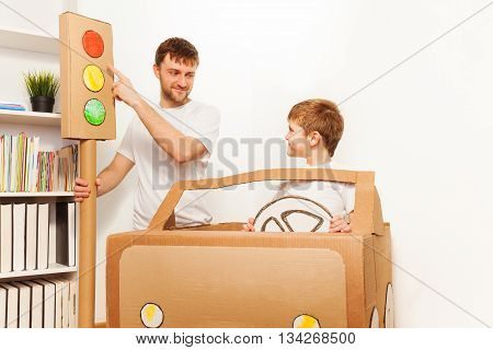 Dad explaining traffic regulations to his son, pointing to the red light signal, as they playing drivers with cardboard car at home
