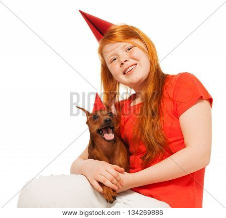 Red girl with long hair sit with her little do in party caps isolated on white