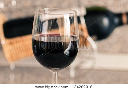 Red wine in a glass bottle on the background on the table